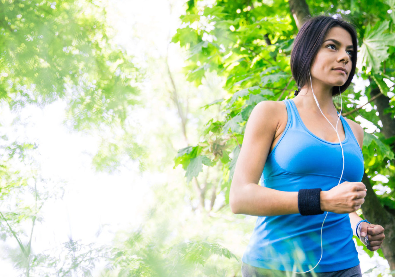 Pretty fitness woman in headphones running outdoors in park. Looking away